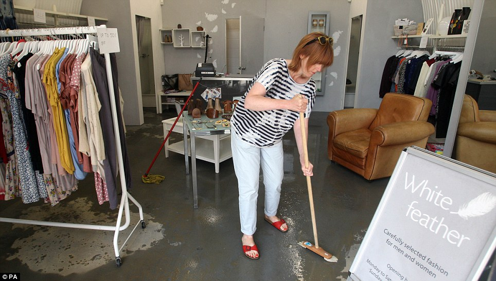 Dealing with it: Sheena Crilly mops up in her shop White Feather after flooding following a water mains bursting in Herne Hill, South London