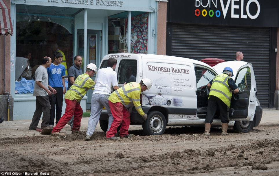 Stuck in the mud: Rescuers have had to battle to free vehicles from the dirt and debris washed into the street by the flood of water