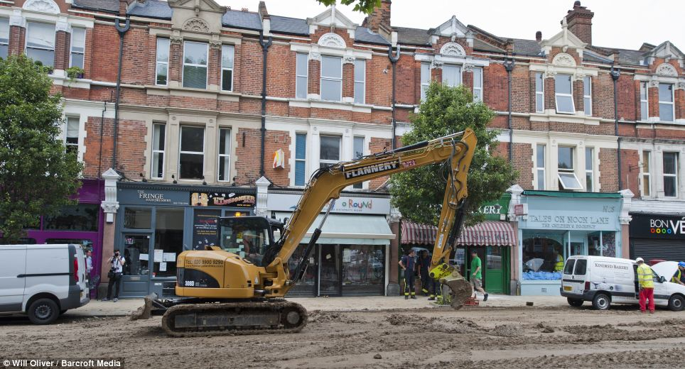 Drafted in: Diggers are brought to help with the clean up effort on Herne Hill