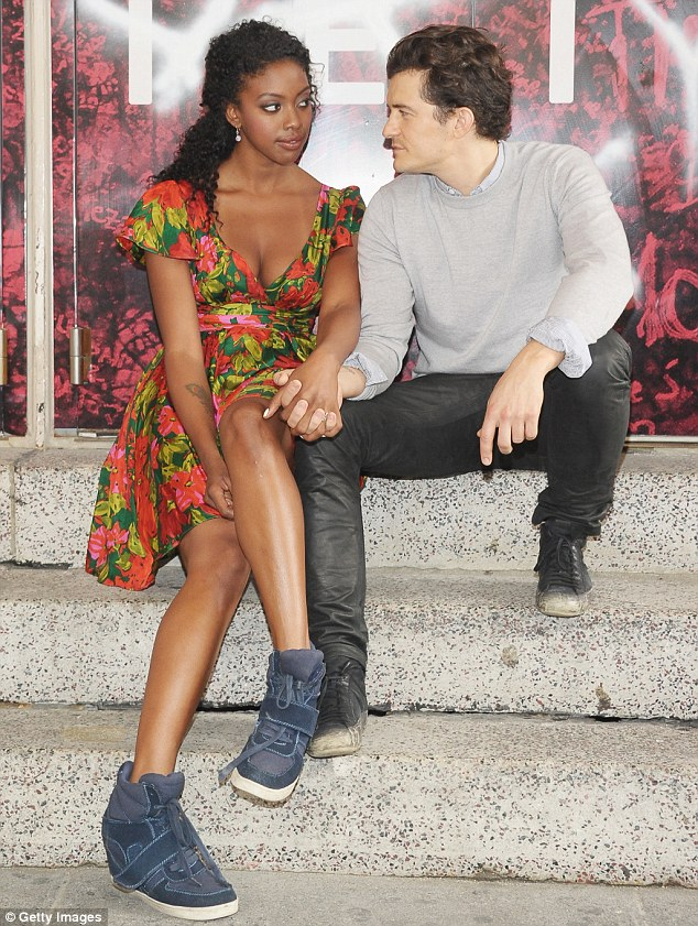 Holding hands: The duo held hands as they posed for the cameras whilst sitting on a set of stairs