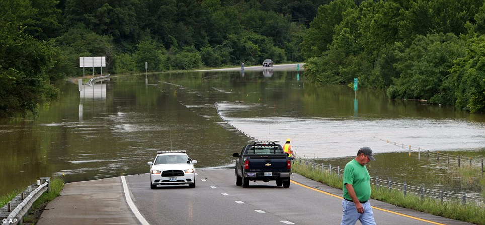 No go: Missouri Department of Transport and State trooper workers guarded and assessed the flooded main road, and advised all drivers not to attempt to cross flooded roads
