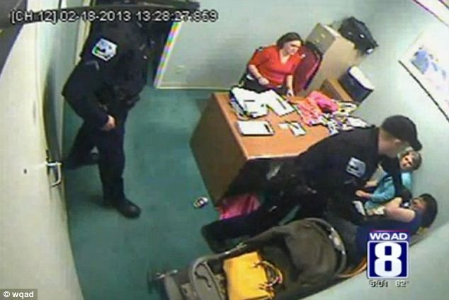 Attack: A police officer, named as Scott Crow, lunges at shoplifter Brandie Redell at a Von Maur store in Iowa on February 18