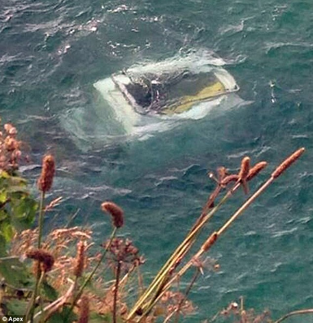 Ransacked: Mr Hill's submerged Land Rover which couldn't be recovered until the low tide came in this morning when it had already been looted by snorkelers overnight