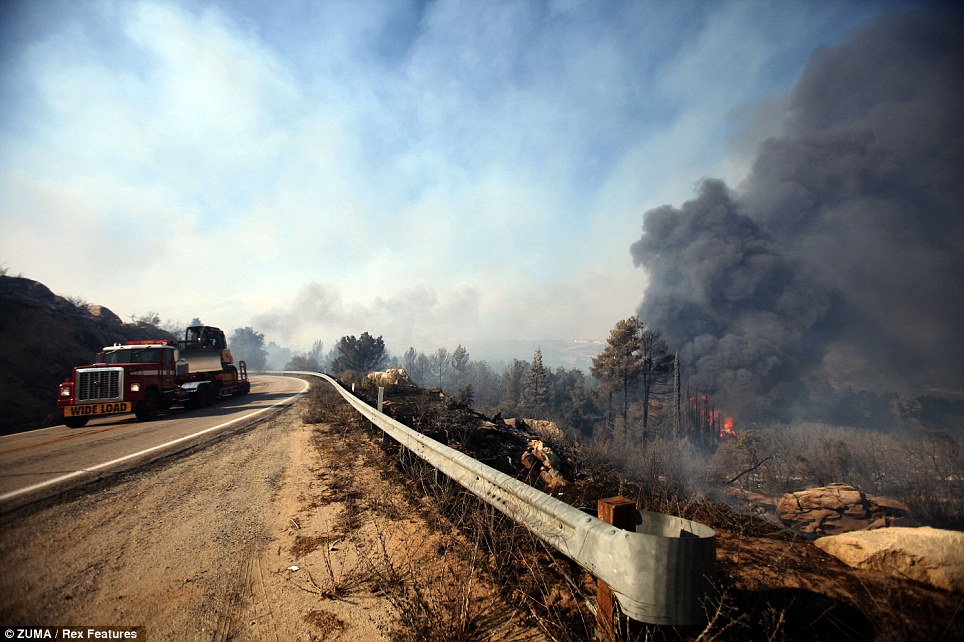 Creeping closer: Thick plumes of smoke and flames can be seen close to a highway