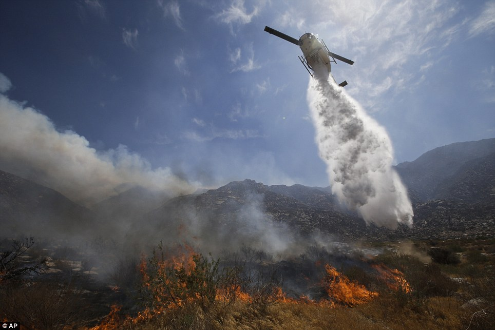 Battling the blaze: A helicopter drops gallons of water over Cabazon in California as wildfires spread