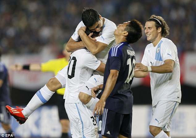 Smiling again: Suarez is lifted up by team-mate Alvaro Gonzalez, who scored Uruguay's fourth goal