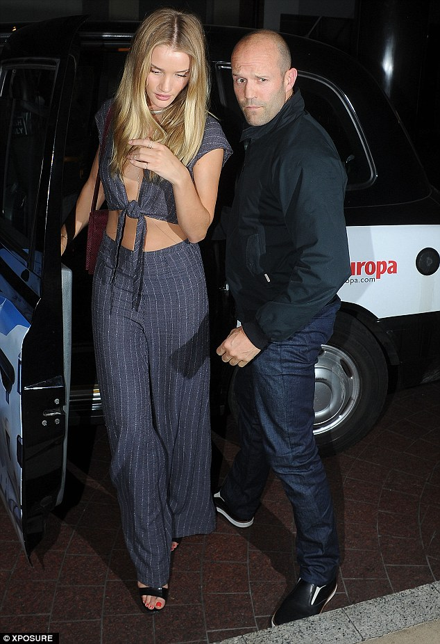 Jason Statham escorts Rosie Huntington-Whiteley out of their cab on Thursday evening