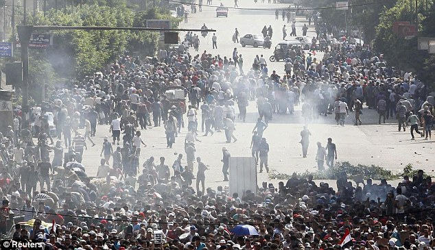 Unstable: Protestors run away from tear gas during clashes in Cairo