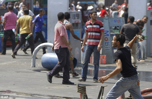 Angry: Supporters of Morsi throw stones at a gasoline station that belongs to the Egyptian Army in Cairo