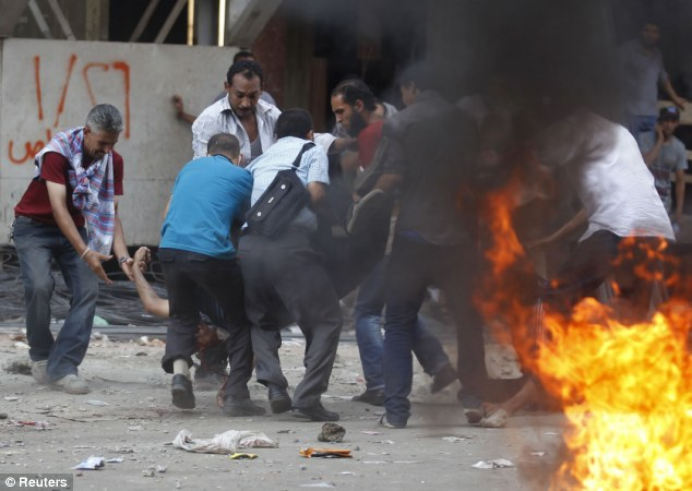 Police violence: Morsi supporters carry an injured demonstrator during clashes outside Azbakeya Police Station