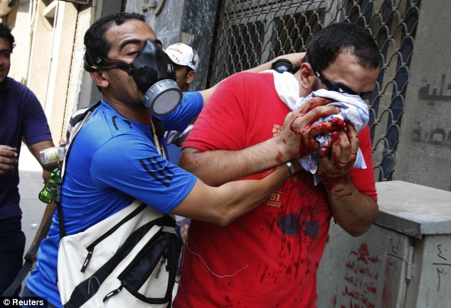 Street battle: A Morsi supporter is taken from the crowd after he was injured during a protest outside Al-Fath Mosque in Ramses Square, in Cairo