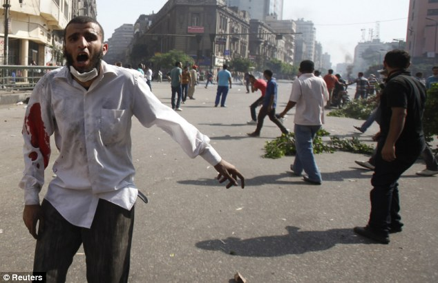 A member of the Muslim Brotherhood and supporter of ousted Egyptian President Mohamed Mursi shouts slogans after being injured during clashes in front of Azbkya police station