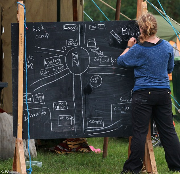 Where to go: One activist chalks up a makeshift map to direct people around the site in the coming days