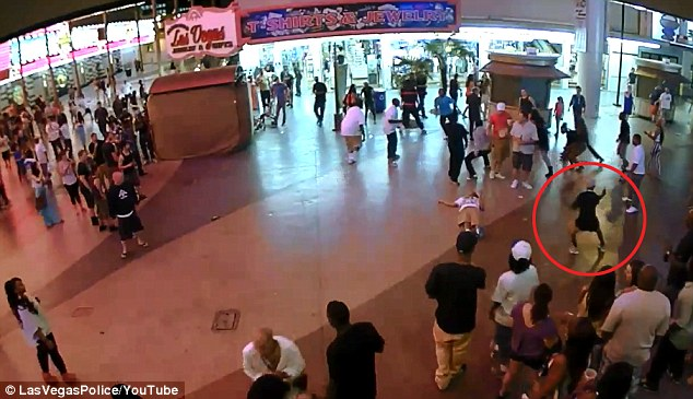 Chaos: With the man knocked out on the floor - the shooter can be seen circled and taking aim at the crowd