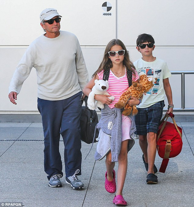 Down to earth: The Douglas family even carry their own bags despite their fame