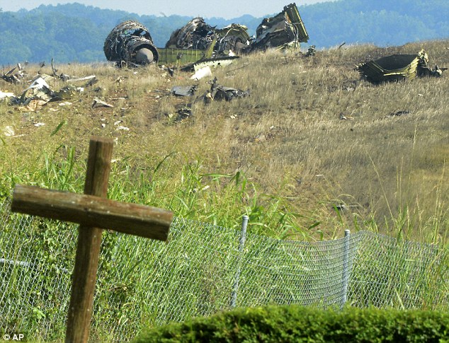 Resting place: A wooden cross by a church is shown near the wreckage of a UPS Airbus A300 cargo plane that crashed on the north side of the Birmingham-Shuttlesworth International Airport