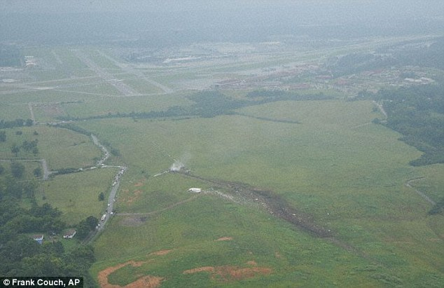 Tricky: This aerial view of the crash site clearly shows the hill and trees that are positioned close to the threshold of runway 18