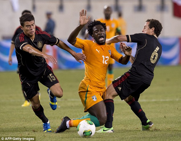 Someone stop him: Bony gets caught between two Mexico defenders while playing for the Ivory Coast