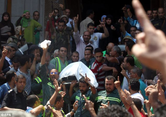 Grim: A stretcher covered with a white blanket is carried out of al-Fateh mosque on Ramses Square, Cairo