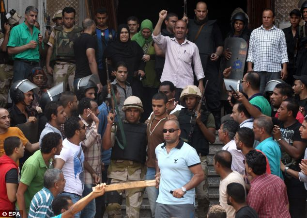 A pro-Morsi supporter is escroted from the mosque