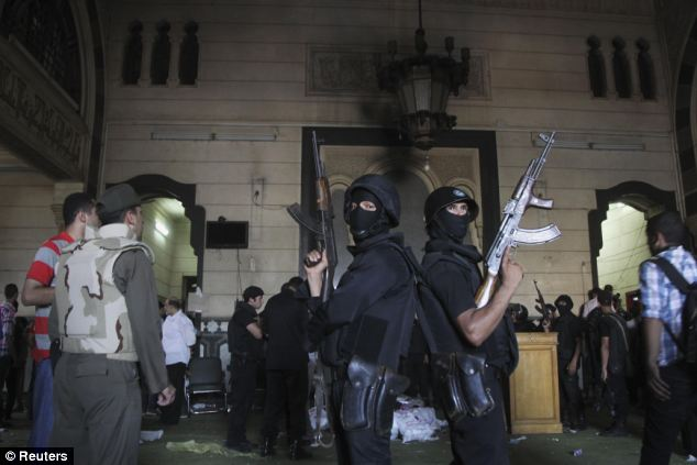 Policemen stand guard inside a room of the al-Fath mosque