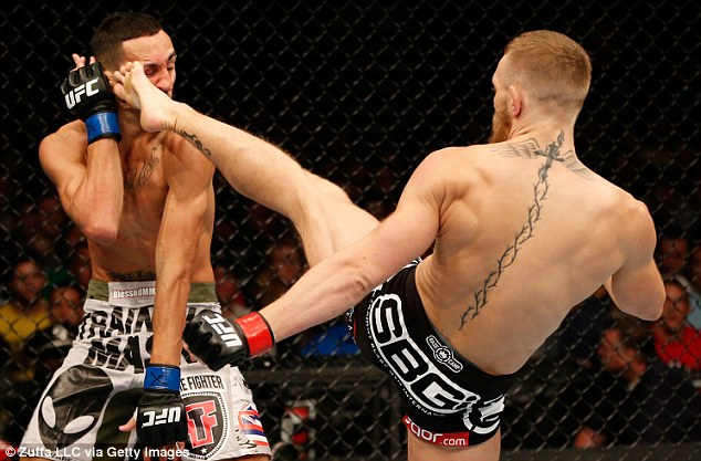 Head to toe: Conor McGregor connects with a kick to Max Holloway's face