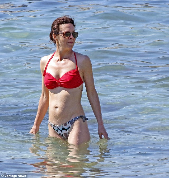 Sea goddess: Helen McCrory looked a vision in a red bikini top and pattered bottoms as she waded through the waves