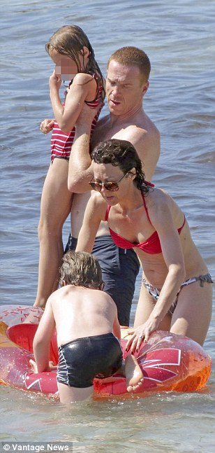 Taking turns: Helen helps her son into the rubber boat whilst Damian takes their daughter out as they take turns on the beach day