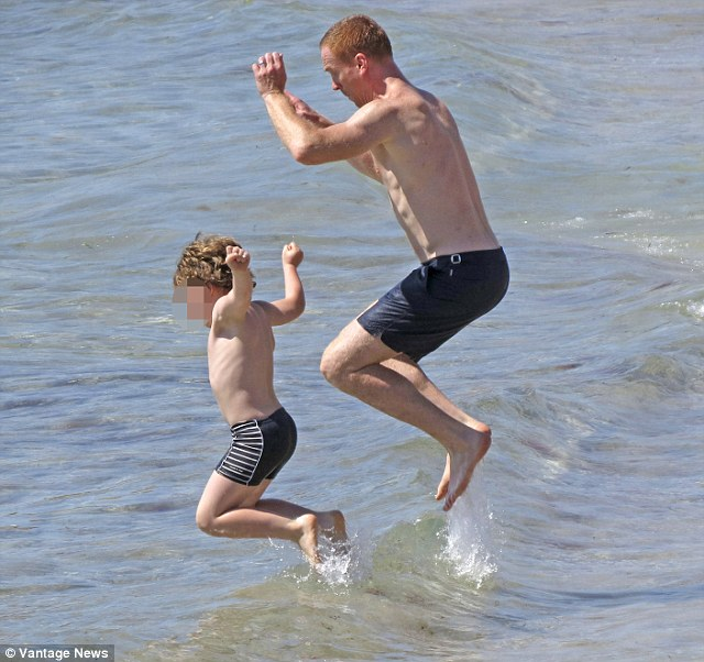 Jump for joy: Damian shows just what a fun dad he is as he and his son jump over waves together on the beach