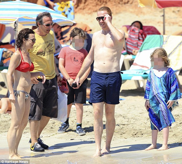 All smiles: Damian smiles as he enjoys his day at the beach with his family