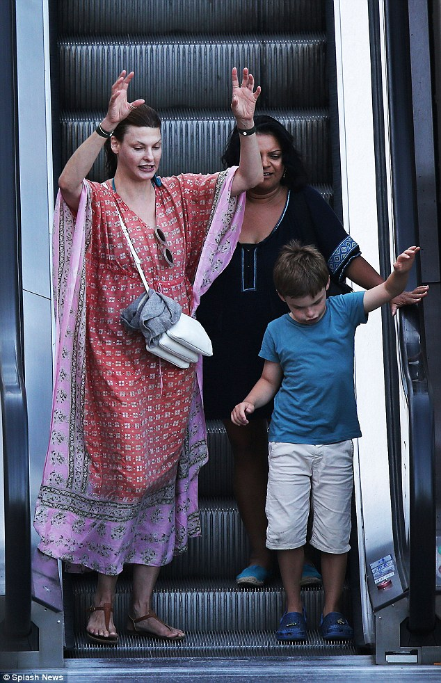 Larking around: the supermodel seemed to be making a game out of riding the escalator with her little boy