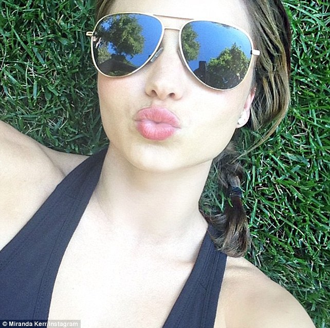That's a pout: Miranda Kerr posts a 'selfie' on Twitter whilst enjoying a relaxing park day with her son Flynn