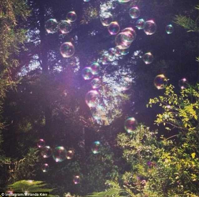 Blowing bubbles: Miranda Kerr was blowing bubbles in the open air with son Flynn