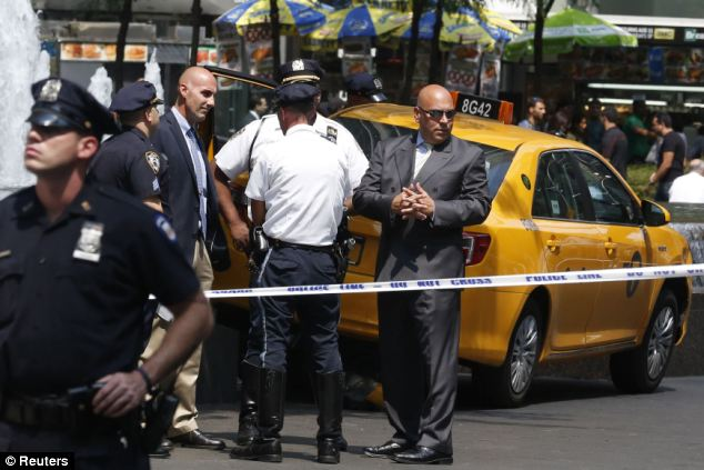 Probe: New York City Police officers investigate the scene after the dramatic crash at 11am Tuesday