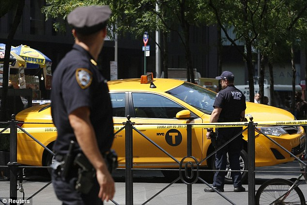 New York City Police officers investigate the taxi cab that jumped the curb