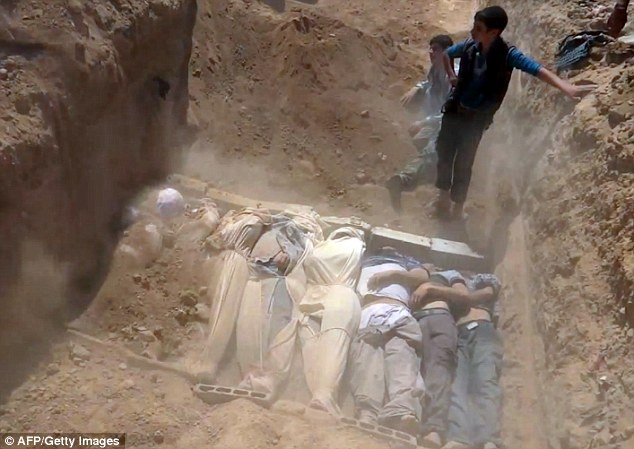 This image grab taken from a video uploaded on YouTube allegedly shows Syrians covering a mass grave containing bodies of victims of the attack
