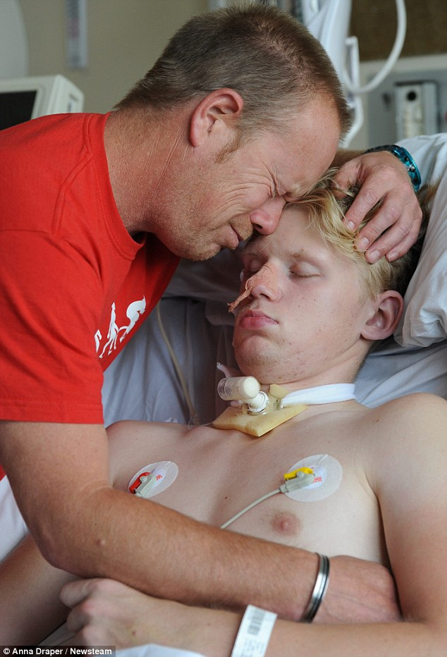 A father's anguish: Mark Smith gently cradles 16-year-old Ryan in hospital where he lies in a coma