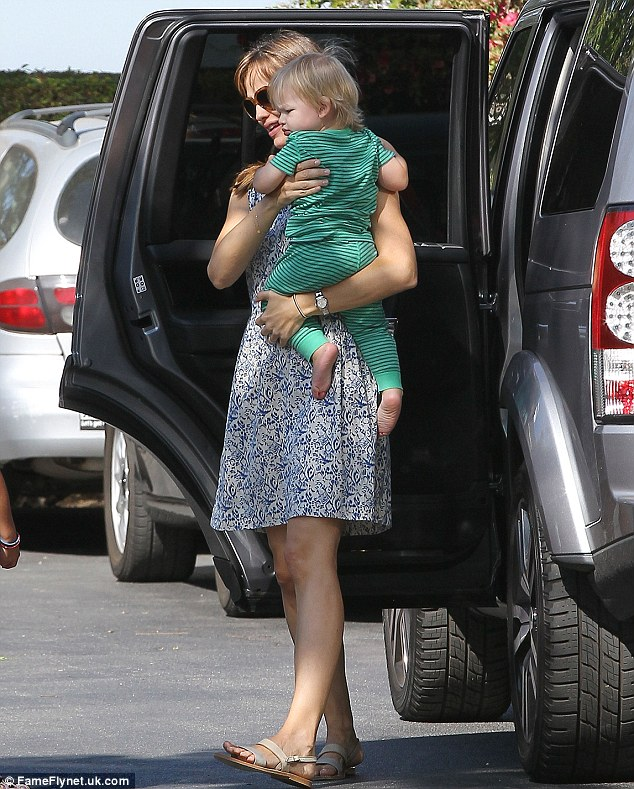 Errands: Jennifer carefully takes a sleepy looking Samuel out of his car-seat as they stop off to run some errands in Los Angeles