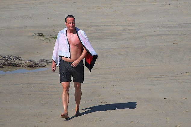 Contemplation: Mr Cameron looks thoughtful as he walks along the beach