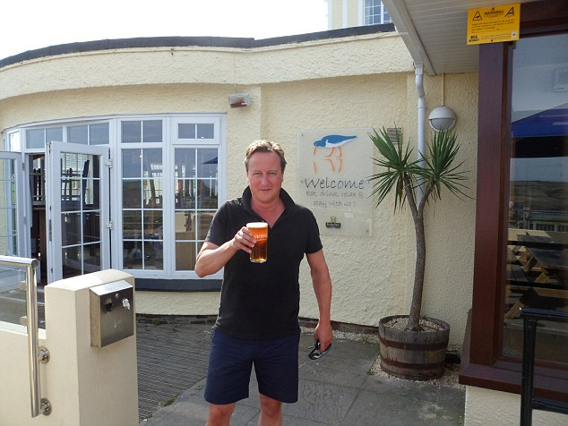 David Cameron looked relaxed as he enjoyed a pint of local Tribute Ale at the Oyster Catcher bar in Polzeath, Cornwall yesterday