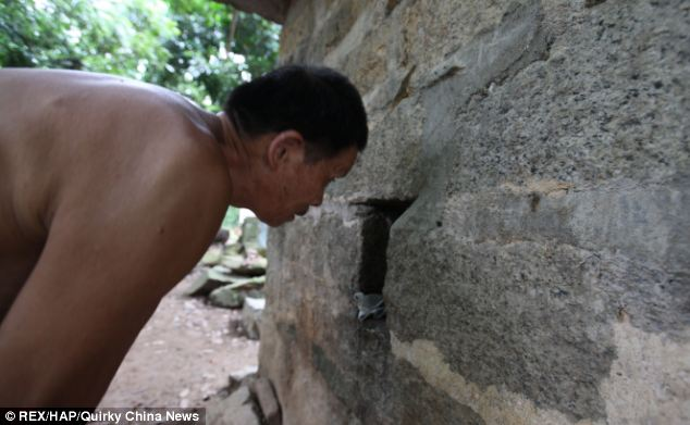 Inhumane: Dong Waitou peeks through a hole in the stone wall to check on his son, who has not left the stone hut in 30 years