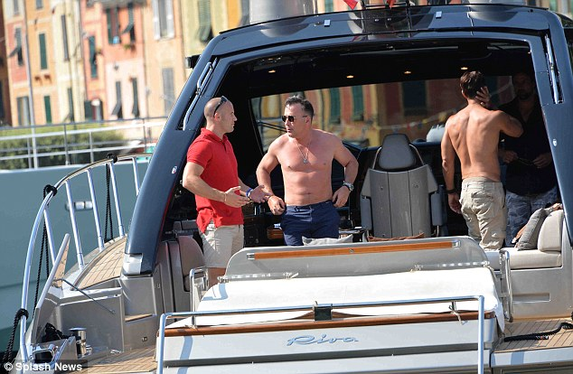 David Furnish stands on deck as his boat arrives at the picturesque Italian harbour on Friday