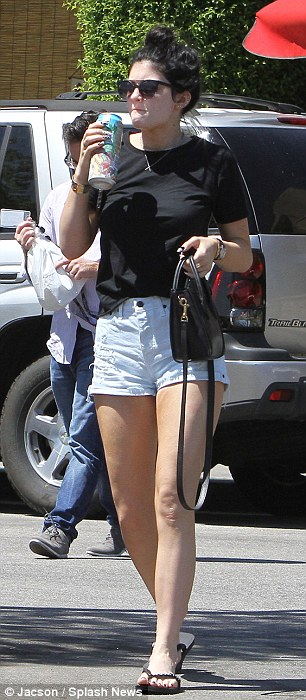 Different look: For lunch the reality star completely changed donning a pair of high waisted blue denim shorts, a black T-shirt and a pair of flip flops