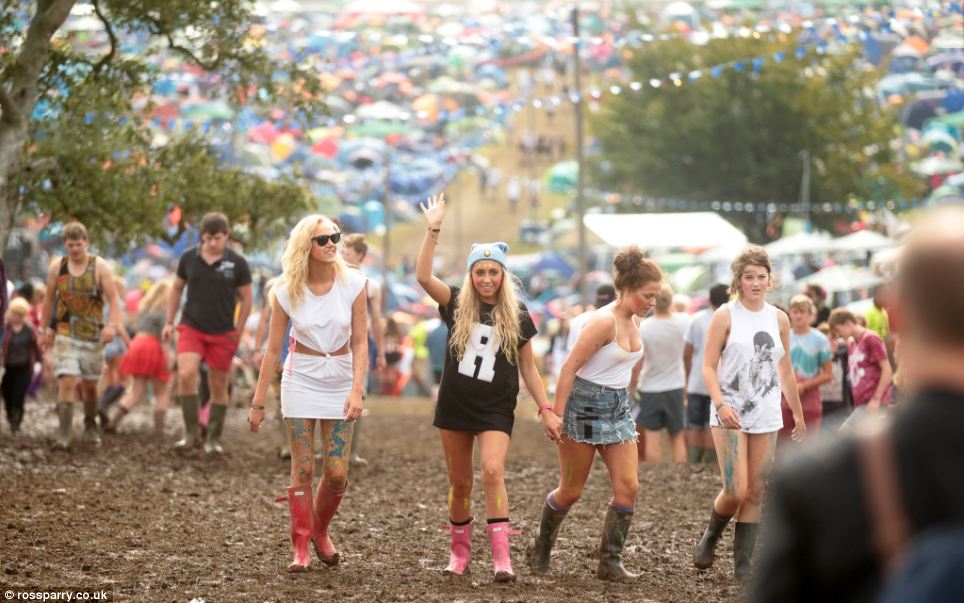 Ready to rock! Festival goers are already mucky as they traipse across the sloppy conditions - but that doesn't stop them enjoying themselves