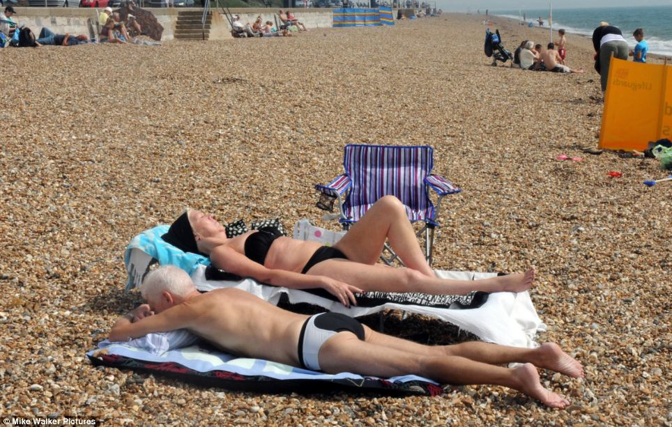 Top up the tan: This couple soaked up some sunshine at Southsea, not seeming to mind the pebbly beach