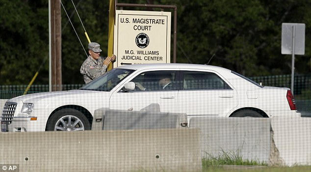 Verdict Delivered Today: A guard raises the gate to for the stand-by defense lawyers heading to the court martial of Maj. Nidal Malik Hasan - on Friday