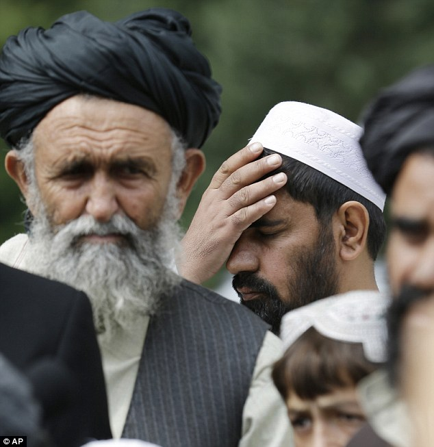 An Afghan villager holds his head as he and others attend a news conference. Many of the witnesses had several family members killed by Bales