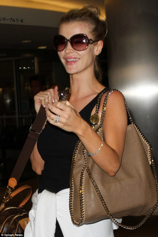 Natural beauty: The make-up-free star hid her tired eyes behind large brown sunglasses and flashed her impressive wedding bling as she strolled through the airport