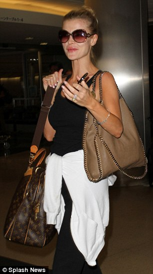 Frequent flyer: The Polish model wore comfy black sweat pants, a black singlet top and matching Tory Burch sandals for her flight, with a white hoodie tied around her waist