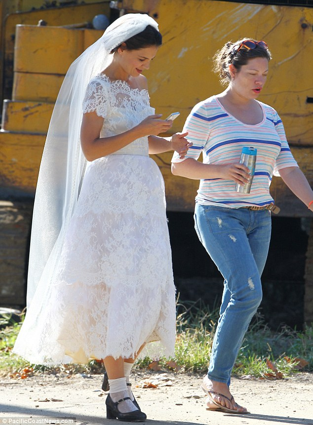 Here comes the bride: The 34-year-old was distracted by her phone as she walked to set with an assistant